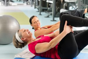 Fitness center senior woman exercise sit ups with personal trainer