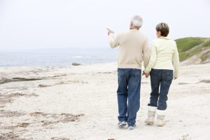 Couple at the beach holding hands and pointing