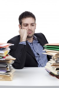 young businessman looking at stack of files